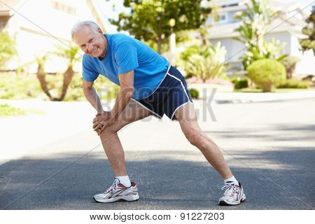 Elderly man warming up for run