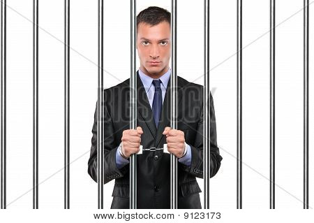 A Handcuffed Businessman In Jail Holding Bars