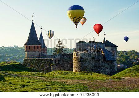 Hot balloons fly above medieval castle. Ukraine Kamenets-Podolsk