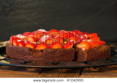 fresh chocolate cake wit red strawberries on wooden table
