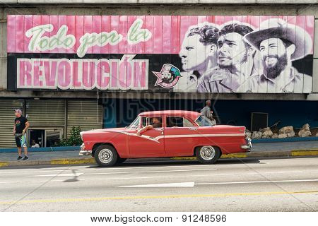 HAVANA,CUBA - MAY 12,2015 :  Vintage american car next to a poster supporting the Cuban Revolution