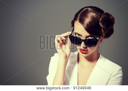 Close-up portrait of a gorgeous young woman wearing retro glasses. Beauty, fashion. Make-up. Optics, eyewear.