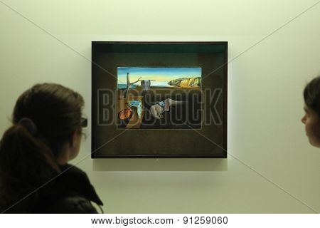 PARIS, FRANCE - JANUARY 7, 2013: Visitors look at the painting The Persistence of Memory (1931) by Salvador Dali displayed at his retrospective exhibition in Paris, France.