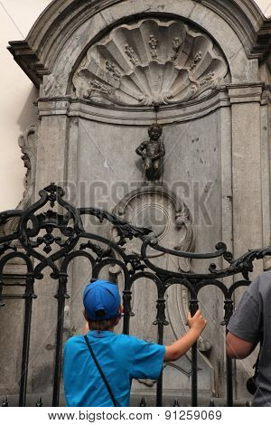 BRUSSELS, BELGIUM - AUGUST 13, 2012: Young boy looks at the Manneken Pis in Brussels, Belgium.