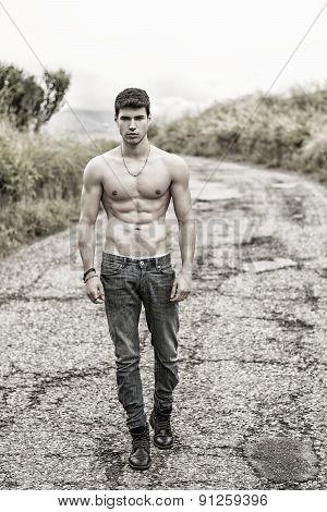 Shirtless muscular young man walking on rural road