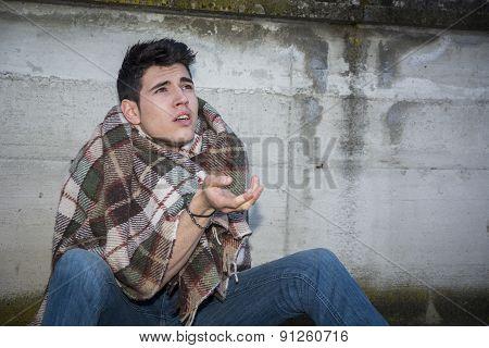 Young male beggar on city sidewalk
