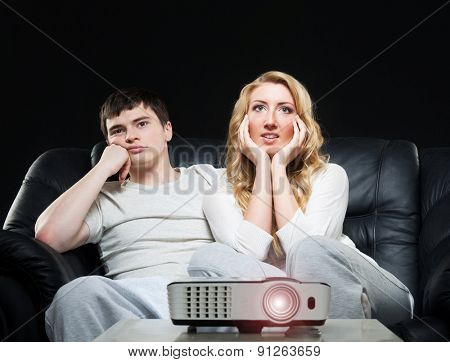 Young couple watching movie or sport broadcast on tv sitting on sofa in living room.