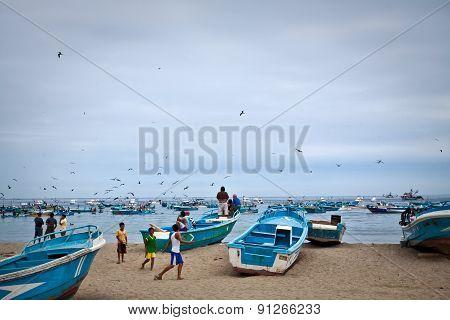 Busy fishermen in the morning along a beach shore, Puerto Lopez, Ecuador