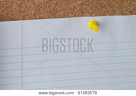 Yellow Thumb Tack Holding Paper On Cork Board