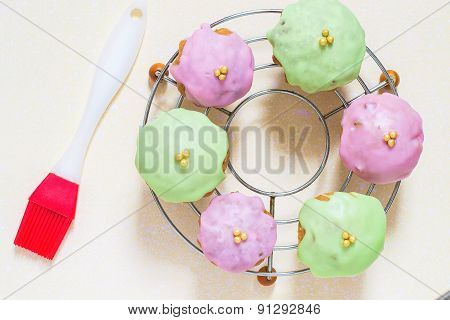 Cupcakes With Colored Glaze On The Grill And Brush