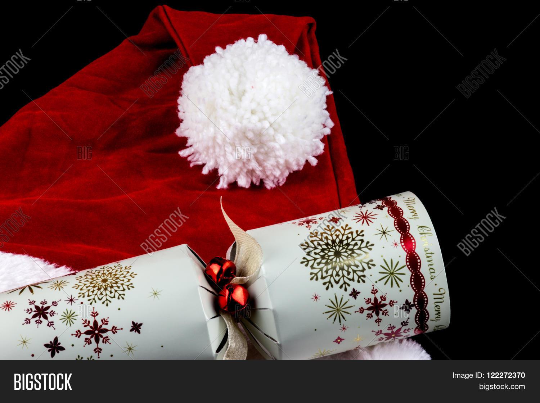 c837fc491c6c0 Christmas santa hat and traditional Christmas cracker on black background