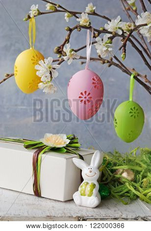 Easter colorful eggs hanging at a blooming branch and gift with easter rabbit on a white wooden table