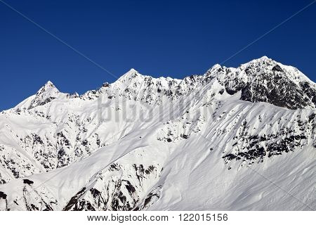 Snowy Mountains And Blue Clear Sky At Sun Day