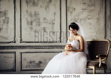 Young bride is sitting in an armchair. Beautiful Bride Portrait wedding makeup wedding hairstyle Wedding dress. Wedding decoration. soft selective focus. gorgeous young bride at interior