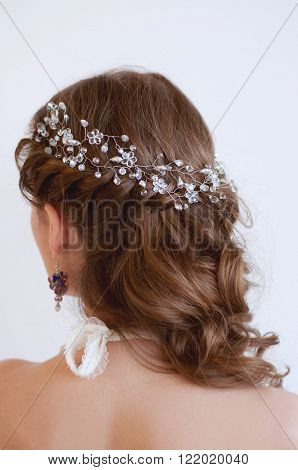 Bridal hairstyle with beaded crystal headpiece on long wavy brown hair