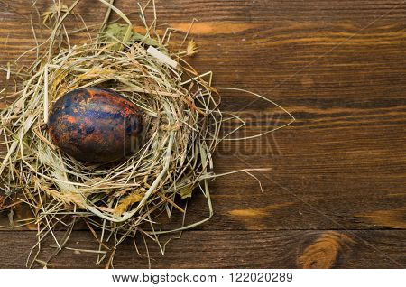 Easter Eggs In The Nest On Wooden Background.