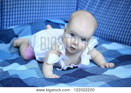 4-months Baby Girl Lying On A Coverlet In White Dress With Ribbons