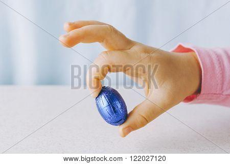 Child's Hand Holding Blue Easter Egg
