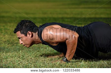 close up of workingout man doing push up on green grass