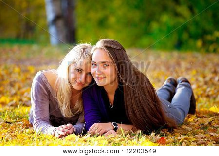 two beautiful teenage girls hugging in the autumn park