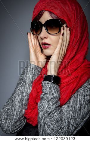 Woman wearing a Hijab head scarf.  This style is a combination of conservative religious styles and modern fashion. poster