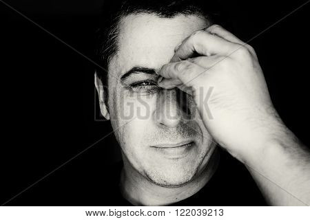 Close up head portrait of a middle aged young looking male in black and white monochrome. The man holds his nose and sinus area with his palm in obvious pain from a head ache in the front forehead area. His expression is discomfort and painful.