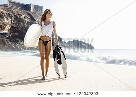 Beautiful young surfer girl walking on the beach