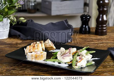 Stuffed turkey breast on the black plate snd wooden background. Chicken roulade