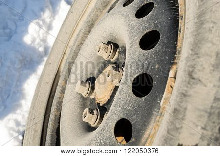 Closeup of car wheel with a removed hubcap. The tires are worn with snow on the ground.