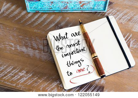 Retro effect and toned image of a fountain pen on a notebook. Handwritten text What Are The Most Important Things To Me ? as business concept image