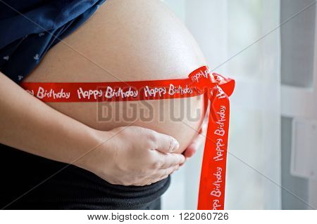 Belly of a pregnant woman with red ribbon