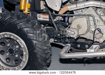 ATV rear wheel of all-terrain vehicle arranged in a row with engine close up