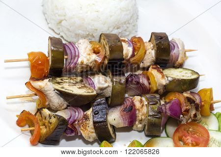 skewers of vegetables and chicken with rice and vegetables
