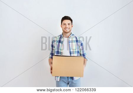 moving, delivery, housing, accommodation and people concept - smiling young man with cardboard box at home