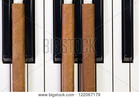 Detail of piano keyboard and luxury cigars