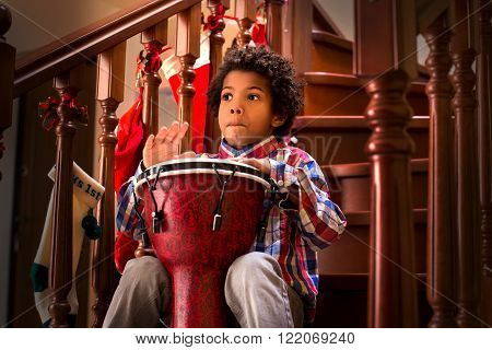 Black kid with drum. Young drum player is playing