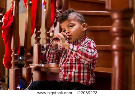 Black boy playing flute on stairs. You've got to have skill.
