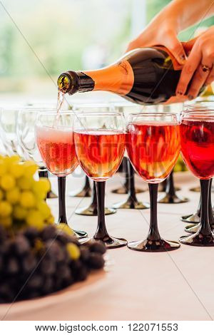 pouring champagne into glasses on a celebratory table