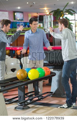 Young men bowling, poised to high five