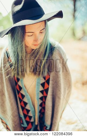 Beautiful young woman in a hat and poncho outdoor