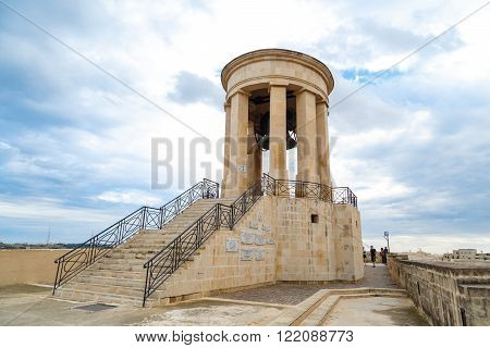 VALLETTA MALTA - OCTOBER 30 2015 : View of the bell tower of Siege Bell Memorial in Valletta Malta on cloudy blue sky background.