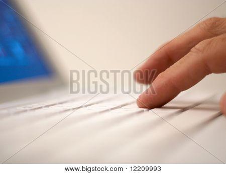 便携式计算机与浅景深。专注于手指触摸笔记本电脑键