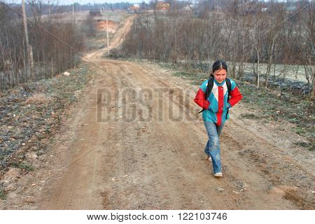 Lipovec village Tver region Russia - May 3 2006: One Russian rural schoolgirl Tanya 11 years old goes to school early in morning in spring in cold weather along a country road in countryside