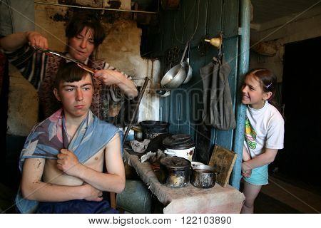 Lipovec village Tver region Russia - May 7 2006: Family Russian farmers in his home Peasant Woman cutting hair of her son in the presence of his daughter 11 years old.