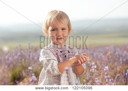 Little girl 2-3 year old wearing rustic style dress. Looking at camera. Posing outdoors. Childhood.