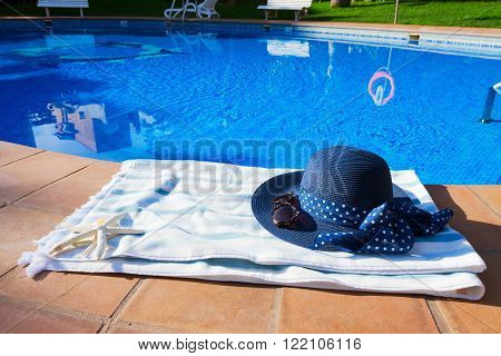 towel and summer hat  near pool at sunny summer day