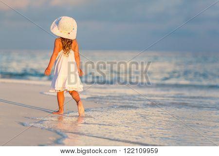 Little girl walking on beautiful ocean beach