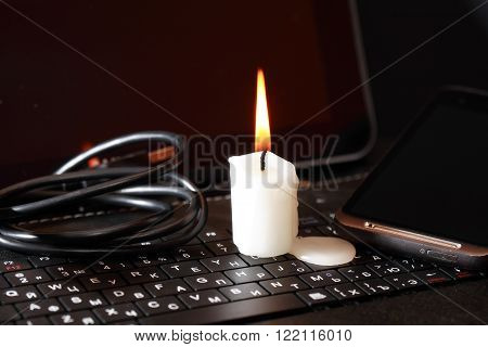 Blackout concept. Lighting candle on laptop near cable