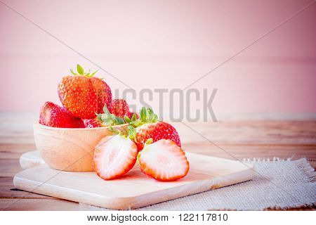 Fresh strawberries on old wooden table .