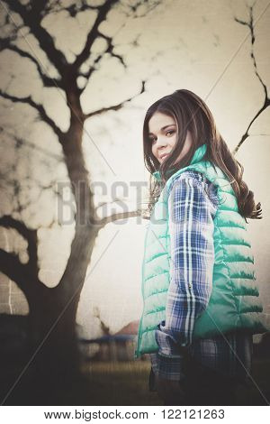 One cute stylish tween caucasian girl turns to look back at camera outside by tree. Filtered